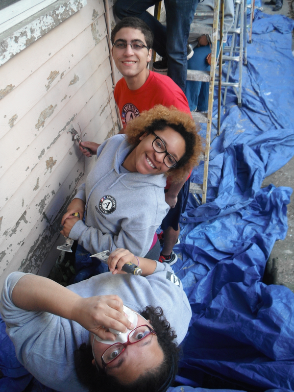 Two AmeriCorps members scraping paint from the side of a house